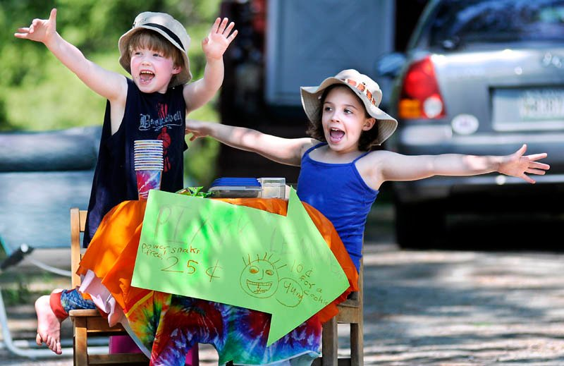 """Sam Hayes, 5, and Emily Hayes, 8, solicit customers Sunday while selling lemonade and cookies along the road at their Mount Vernon home. The business plan was incubated in the kitchen, according to the elder Hayes child. """"I saw lemonade mix in the kitchen and that gave me the idea,"""" she said. Her brother plans to invest his share of profits in the purchase of a toy boat."""