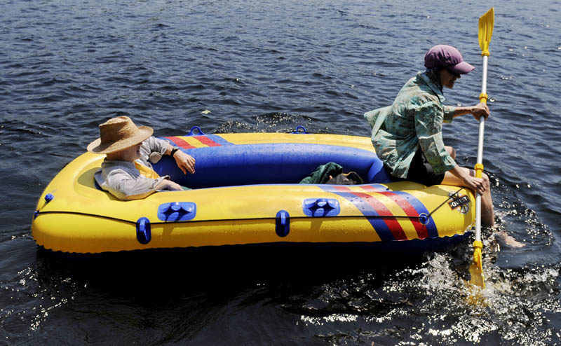 """Tom Swann surveys Minnehonk Lake as Susan Melcher paddles a raft Sunday near their home in Mount Vernon. The couple was working in the garden when high temperatures compelled them to flee to the water, according to Melcher. """"It is hot, hot, hot in the garden,"""" she reported."""