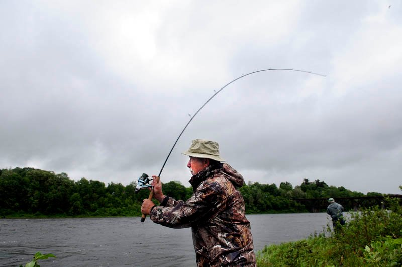 "Dan Levesque, left, of Augusta and Ron Young, of Manchester, cast for striped bass Wednesday on the banks of the Kennebec River in Augusta. Fishing in pouring rain comes naturally to both men, Levesque claims, who cast a line in the river ""seven and half days a week."""