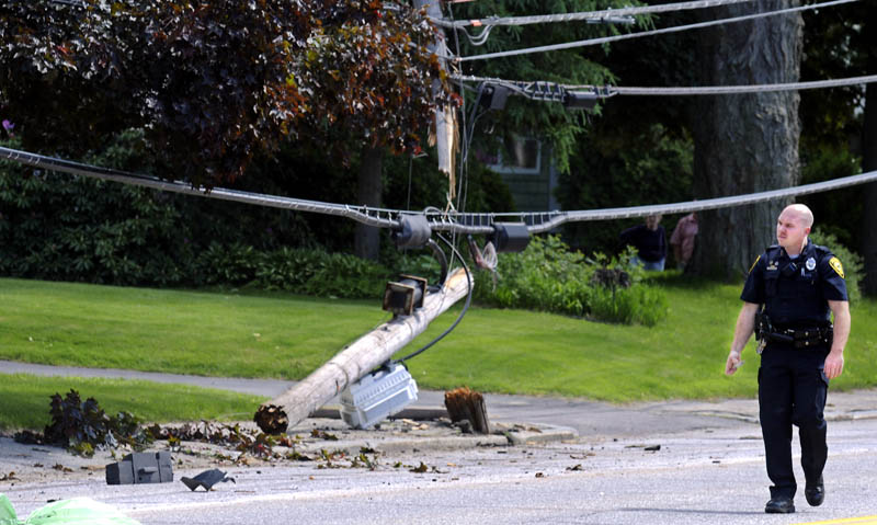 Augusta Police Department Officer Nathan Walker walks past the utility pole that was snapped Monday on Hospital Street, by a car driving in the north lane. A passenger of the vehicle was transported to the hospital following the accident, which was reported just after 2 p.m., according to Walker. The driver, Andrew Pinkham, 34, of Bath, was charged with operating a vehicle after suspension, Walker said.