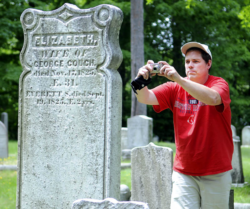 Brad Cushman photographs a relative's gravestone Monday at the Hallowell Cemetery. Cushman and his parents drove up from Burlington, Mass., to examine four Maine cemeteries which contain the remains of relatives.