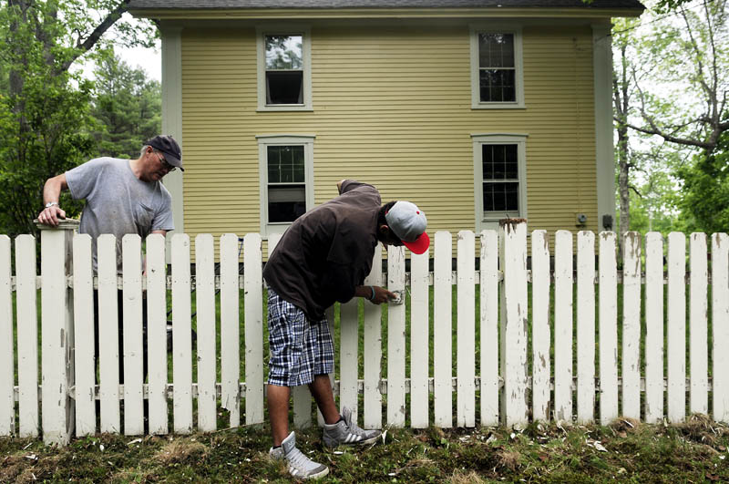 Doug Rooks, left, and his son, Emlyn Rooks-Hughes, scrape down the picket fence at their West Gardiner home on Monday. The duo planned to apply a new coat of paint to the border around their farmhouse, erected in 1805.
