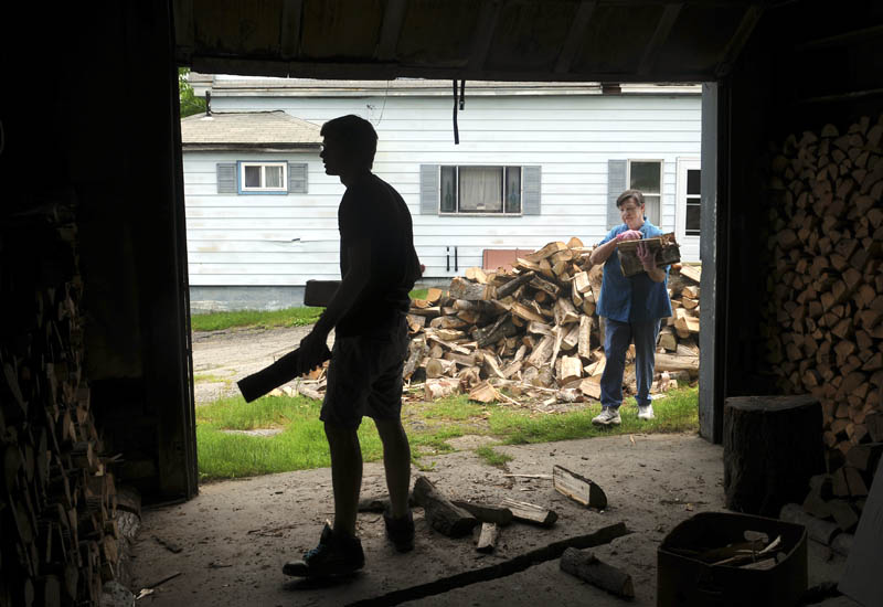 Zach O'Ben, left, stacks firewood with his grandmother, Pauline O'Ben, in the garage of her Gardiner home on Monday. The elder O'Ben said she dries the wood for a year before burning it, and the stacking goes much faster with the assistance of her grandson.