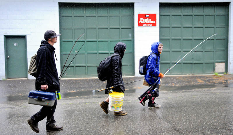 "Nick Crocker, 16, left, Dylan Young, 13, and T.J. Ladd, 20, walk to their Augusta homes in the rain Tuesday after a fishing trip to the banks of the Kennebec River. The trio casts lines almost every day ""except for thunder and lightning,"" Ladd said."