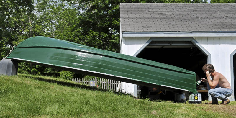Micah Moore of Rhode Island paints the hull of his family's aluminum boat Sunday outside their summer home on Mill Pond in Wayne. Moore and his father, Brian, plan to cruise up to Pocasset Lake to visit their extended family.