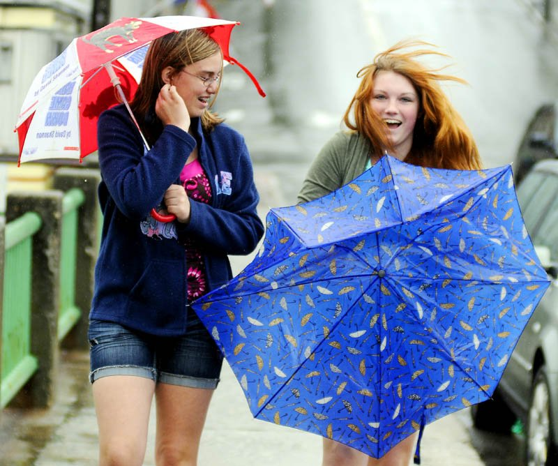 Olivia Turner collects her deflated umbrella Tuesday while walking to lunch with Devon Hall in Gardiner. The Gardiner Area High School students were celebrating their last day of school for the year with a stroll through the rain. Rain and brisk winds are forecast to persist for the rest of the week.