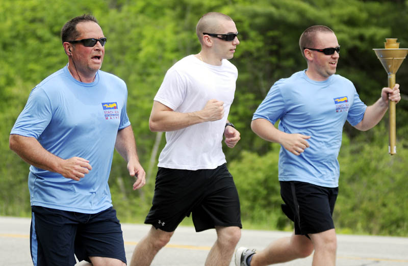 Parole and Probation officer Mark Fortin, left, and Gardiner Police officer Chris Balestra, center, and Gardiner Police Det. Mike Durham run down Route 201 in Gardiner Thursday while participating in the law enforcement torch run to benefit the Maine Special Olympics. Police from across Maine are escorting the torch from Kittery to the University of Maine in Orono to raise funds for the annual competition for people with special needs. Fortin and the Gardiner officers collected the torch at the Richmond line from Johanna and Norman Stickney and handed it off to Hallowell Police Chief Eric Nason in Farmingdale who carried it to Augusta, where the police ran with it Vassalboro. The run should take three days.