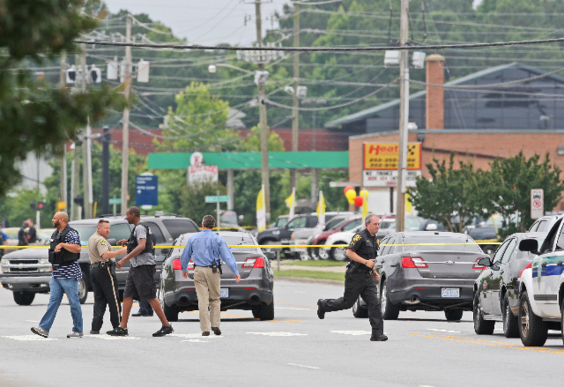 Police investigate the scene of a shooting Friday in Greenville, N.C. A man armed with a shotgun wounded one person at a law firm, then shot three more people across the street in a Walmart parking lot.