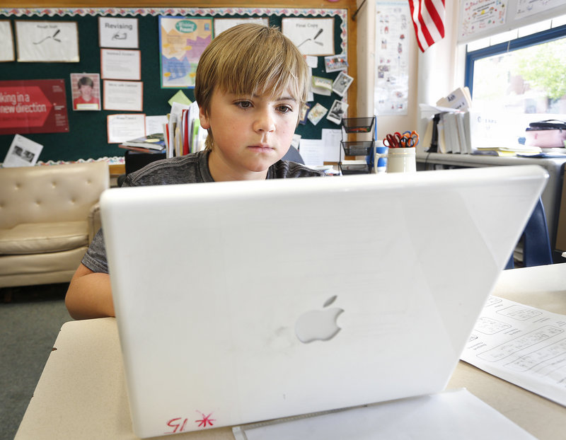 Sixth-grader Cole McGhie works on an Apple laptop computer May 27 during class at King Middle School in Portland. Microsoft and Hewlett Packard are making strong pitches to win Maine's public-school laptops business.