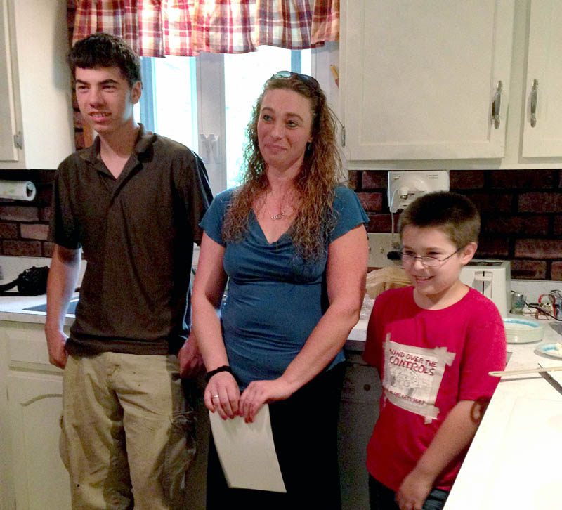 New homeowner Stephanie Basford, 37, stands in the kitchen of her first home with two of her three sons, Ryan Basford, 17, and Cameron Robbins, 9. With help from the U.S. Department of Agriculture, Basford was able to move her family out of a dangerous mobile home and into a house with enough room for her three boys.