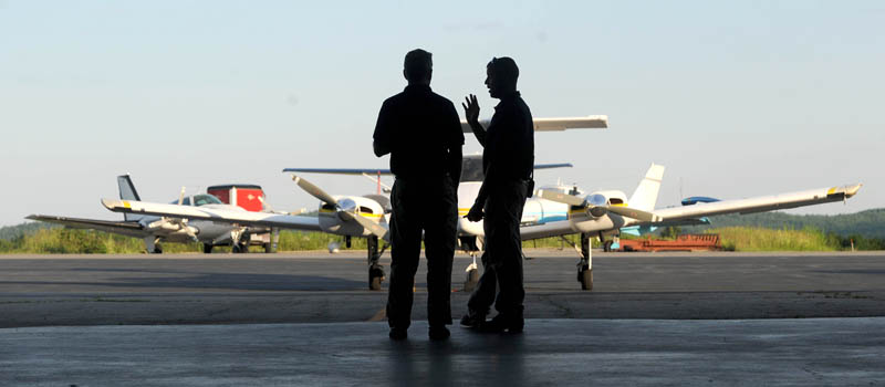 Bruce Olson, owner of Tree Spirits and a Mid-Maine Chamber of Commerce member, speaks with Robert LaFleur Municipal Airport manager Randy Marshall Jr. at the newly renovated airport in Waterville, for a Business After Hours event on Wednesday.