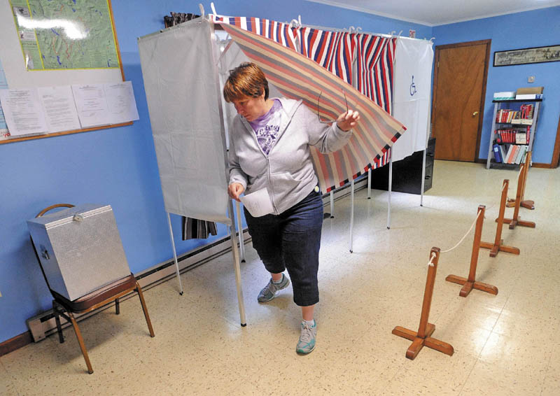 Wendy Belanger, 45, exits the polling booth at the Moscow Town Office on Tuesday after voting on the Regional School Unit 18 budget.