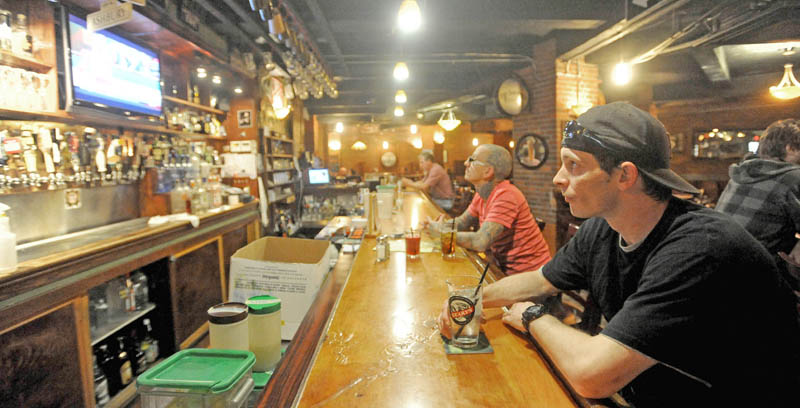 Deon Bennett, 36, far right, sips on a drink as he waits for his lunch at Mainely Brews on Main Street in Waterville on Friday. The Legislature's budgeting committee on Friday proposed a 1 percent increase of the meals and lodging tax, and a 0.5 percent increase of the sales tax.