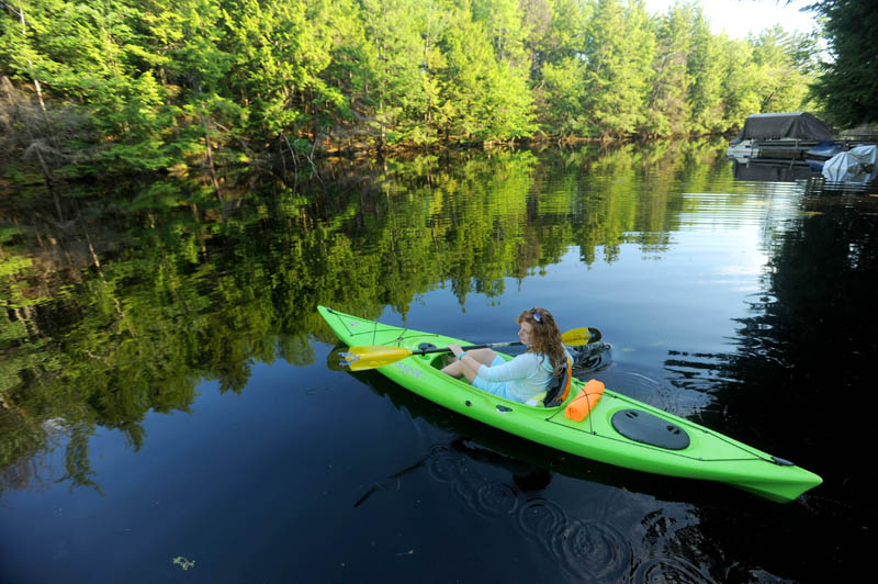 Christine Keller paddles along the Serpentine waterway, a three-mile waterway that cuts across a peat bog as it connects East and North ponds, on Thursday. Speeding boaters and personal watercraft operators along the Serpentine waterway may be unwittingly threatening a comeback by the sandhill crane, a species that recently returned to Maine after being pushed to the brink of extinction. A speed buoy has been installed at both ends of the Serpentine waterway to help control boat traffic.