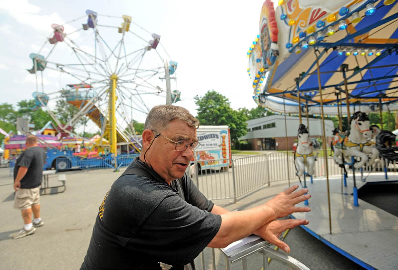 Stephen Dixon, a state fire marshal's office inspector, inspects a merry-go-round at the East Coast Midways carnival in Fairfield on Tuesday.