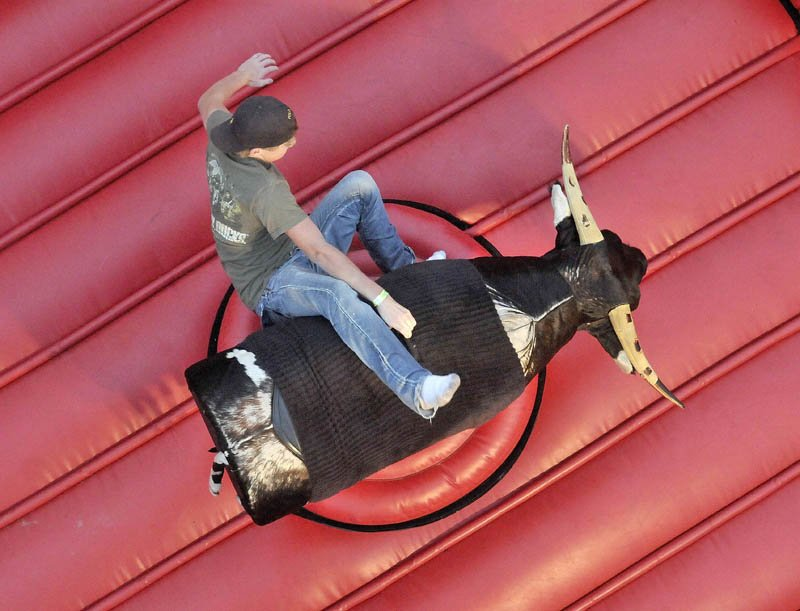 Caleb Patten, 15, tests his strength on the mechanical bull at the East Coast Midways carnival in Fairfield on Thursday.