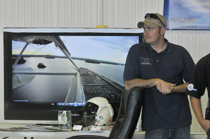 Matt Sylvester of Airlink LLC, a pilot training school at Robert LaFleur Municipal Airport, offers free training simulator rides at the newly renovated airport in Waterville, during a Mid-Maine Chamber of Commerce Business After Hours event on Wednesday.