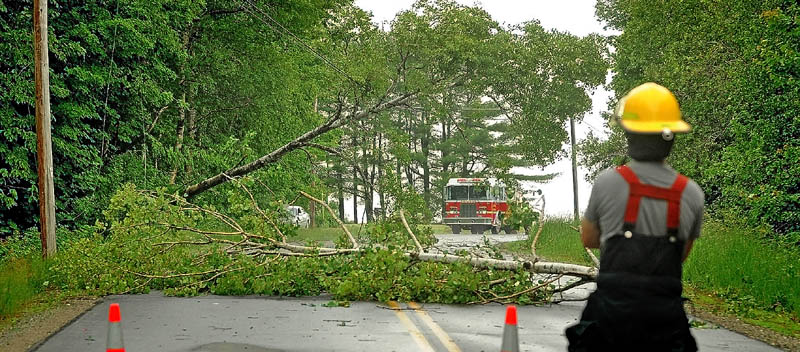 Lloyd Cole, right, with the Madison Fire Department stands by a closed section of Russell Road in Madison on Tuesday, after a thunderstorm knocked down trees and power lines.