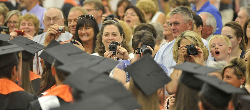 Friends and family take photos of the Winslow High School class of 2013 as they march in to Wadsworth Gymnasium during commencement ceremonies at Colby College in Waterville on Wednesday.