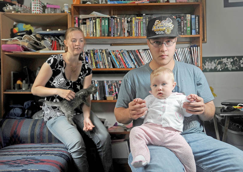Kevin Hardy is one of two males to graduate from the Teen Parent School program at the Maine Children's Home for Little Wanderers in Waterville. With him is his infant daughter, Zoey, and fiancee, Wendy Joler, at Hardy's mother's Winslow residence on Friday.