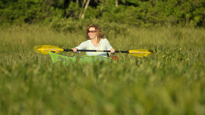 Christine Keller paddles through a section of the Serpentine waterway, a three-mile waterway that cuts across a peat bog as it connects East Pond and North Pond, on Thursday.