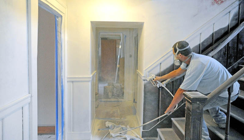 Mike Gough primes the walls during renovations of upstairs apartments in the former Levine's clothing building on Main Street in downtown Waterville. The apartments, once finished, will be rented for around $600 per month.