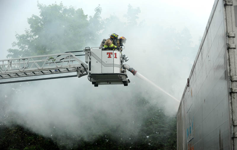 Waterville Fire Department firefighters battle a trailer fire at Pine Tree Pine Tree Waste Services on Airport Road in Waterville, after a powerful thunderstorm rolled through central Maine on Wednesday. The fire was believed to be caused by a lightning strike.