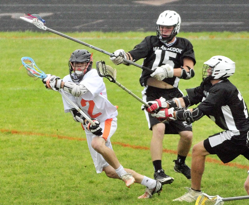 TAKE THE SHOT: Gardiner's Keegan Smith, left, goes in for a shot in front of Maranacook/ Winthrop's Simon Davis, center, and Zachary Godbout during the Tigers' 13-9 win in an Eastern B semifinal game Friday at Hoch Field in Gardiner.