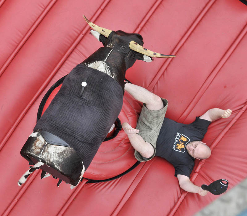 Dan Cahoon, of Oakland, gets thrown from the mechanical bull at the Water Street carnival during the Fairfield Days Community Festival on Saturday.