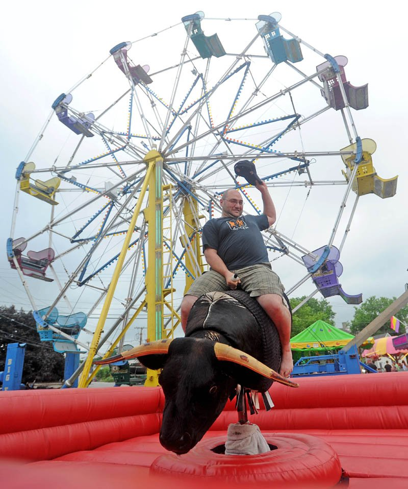 Dan Cahoon, of Oakland, rides the mechanical bull at the Water Street carnival during the Fairfield Days Community Festival on Saturday.