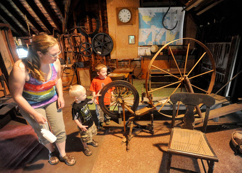 Nikkia Finnemore, 30, left, and her children, Kristpher, 3, center, and Benjamin, 5, right, tour the barn at the Cotton-Smith House on High Street in Fairfield during the Fairfield Days Community Festival on Saturday.