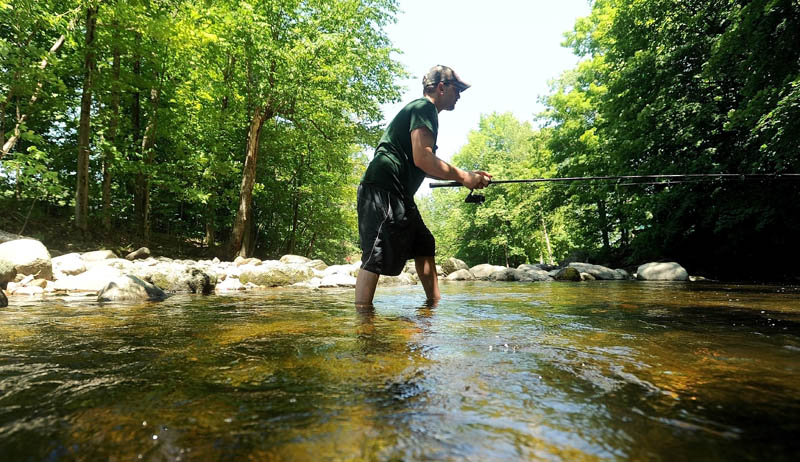 """Dan Tracy, 28, of Oakland, takes advantage of the sunny weather and fishes the Messalonskee Stream just below Messalonskee Lake in Oakland on Friday. """"The kids are at the grandparents, which means I'm going fishing,"""" Tracy said."""