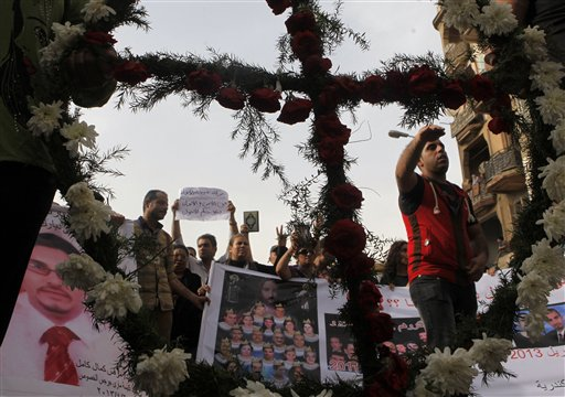 Egyptian Christian are seen through a cross during a memorial march for the killed Christians in clashes between Muslims and Christians in April in Cairo, Egypt, on May 24.