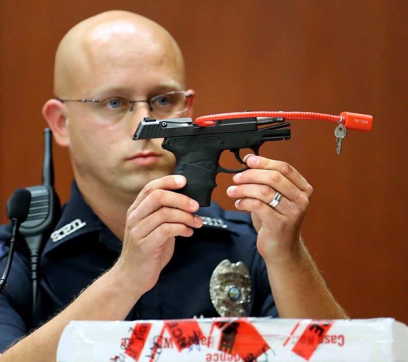 Sanford, Fla., police Officer Timothy Smith holds up the gun that was used to kill Trayvon Martin, while testifying in the George Zimmerman trial in Seminole circuit court in Sanford, Fla., on Friday.