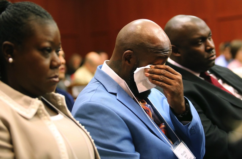 The father of Trayvon Martin, Tracy Martin, cries as he listens to the description of his son's death during opening statements in the George Zimmerman trial, with Sybrina Fulton, Trayvon's mother, left, and Daryl Parks, a family attorney, right, in Seminole circuit court, in Sanford, Fla., Monday, June 24, 2013. Zimmerman has been charged with second-degree murder for the 2012 shooting death of Trayvon Martin. (AP Photo/Orlando Sentinel, Joe Burbank/Pool)