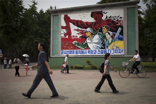 "People walk past a roadside propaganda billboard promoting the ""military first"" policy and a boost to build the country's economy in Pyongyang, North Korea, on Sunday."