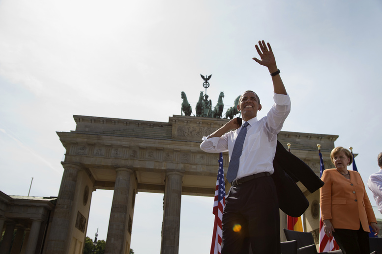 President Barack Obama, accompanied by German Chancellor Angela Merkel, waves to the crowd after speaking at the Brandenburg Gate in Berlin on Wednesday.