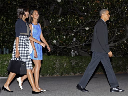 President Barack Obama, first lady Michelle Obama, and daughter Malia walk to Marine One on the South Lawn of the White House in Washington on Sunday, as they head to Northern Ireland for the G-8 Summit.