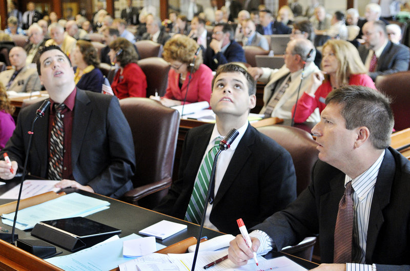 Representatives Kenneth Fredette, right, R-Newport, Alexander Willette, R-Mapleton, and Tyler Clark, R-Easton, watch the vote in the House of Representatives on Wednesday, June 26 to override Gov. Paul LePage's veto of the state budget. Fredette and Clark voted to overturn the veto, while Willette voted to uphold the veto.