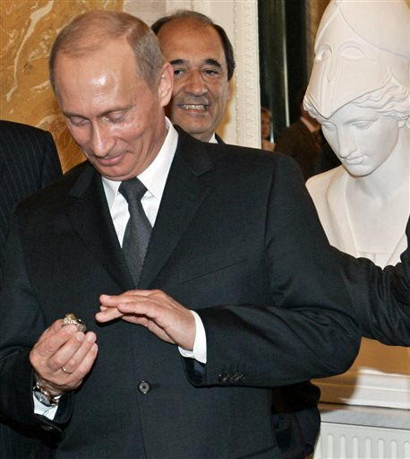 In this June 25, 2005, photo, Russian President Vladimir Putin holds a diamond-encrusted 2005 Super Bowl ring belonging to New England Patriots NFL football team owner Robert Kraft during a meeting of American business executives outside St. Petersburg, Russia.