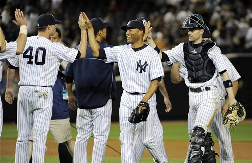 New York Yankees pitcher Mariano Rivera and catcher Chris Stewart, right, celebrate with teammates after the Yankees defeated the Boston Red Sox, 4-1, in a baseball game Friday, May 31, 2013, at Yankee Stadium in New York. (AP Photo/Bill Kostroun)