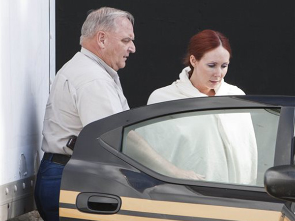 In this June 7, 2013, photo, Shannon Richardson is led to a Titus County Sheriff's car after an initial appearance at the federal building Texarkana, Texas. Authorities say Richardson sent ricin-laced letters to President Barack Obama and others in an attempt to frame her estranged husband.