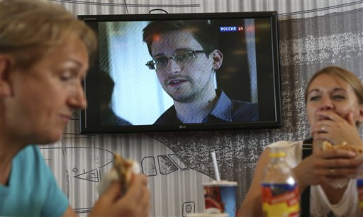 Transit passengers eat at a cafe with a TV screen with a news program showing a report on Edward Snowden, in the background, at Sheremetyevo airport in Moscow Wednesday.