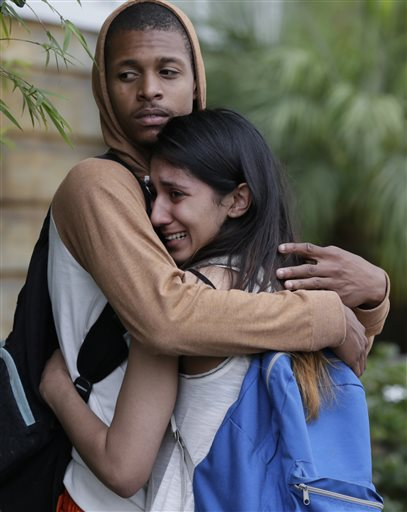 A weeping woman is comforted after being escorted off campus as police swarm Santa Monica City College, where a gunman shot numerous people Friday.