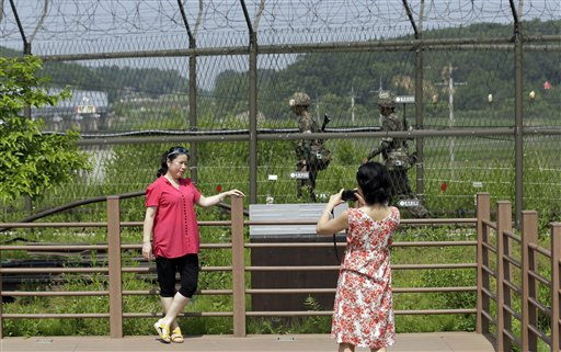 Visitors take souvenir photos as military soldiers patrol at the Imjingak Pavilion near the border village of Panmunjom, which has separated the two Koreas since the Korean War, in Paju, north of Seoul, South Korea, Sunday.
