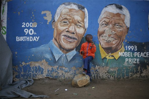 """Hussein Gallo, 7, stands by a mural of Nelson Mandela in the Soweto township in Johannesburg, South Africa, on Saturday. Former South African President Nelson Mandela is in """"serious but stable"""" condition after being taken to a hospital to be treated for a lung infection, the government said Saturday, prompting an outpouring of concern from admirers of a man who helped to end white racist rule."""