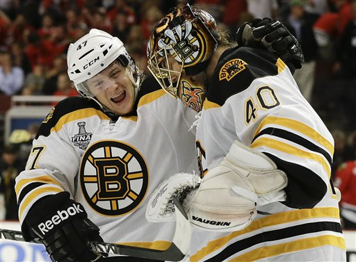 Boston Bruins defenseman Torey Krug (47) celebrates with goalie Tuukka Rask (40) after the Bruins scored a goal against the Chicago Blackhawks in sudden death overtime during Game 2 of the NHL hockey Stanley Cup Finals, Saturday, June 15, 2013, in Chicago. The Bruins won 2-1. (AP Photo/Nam Y. Huh)
