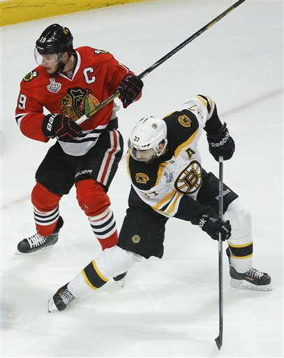 Boston Bruins center Patrice Bergeron (37) looks for a rebound against Chicago Blackhawks center Jonathan Toews (19) in the first period during Game 5 of the Stanley Cup Finals on Saturday in Chicago. Bergeron and Toews are both injured entering Game 6 on Monday.