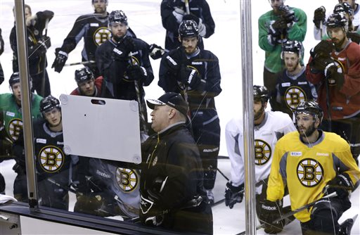 Boston Bruins players gather around head coach Claude Julien as he uses a board during practice at TD Garden in Boston on Monday. The Bruins are preparing to face the Chicago Blackhawks in the Stanley Cup finals with Game 1 scheduled for Wednesday in Chicago. TD Garden