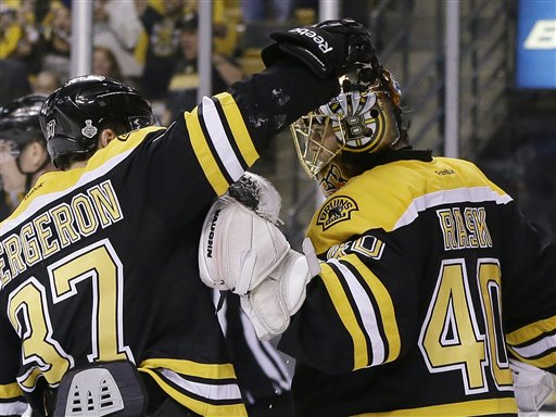 Boston Bruins center Patrice Bergeron (37) congratulates Boston Bruins goalie Tuukka Rask (40), of Finland, on his shutout to beat the Chicago Blackhawks 2-0 in Game 3 of the NHL hockey Stanley Cup Finals in Boston, Monday, June 17, 2013. (AP Photo/Elise Amendola) TD Garden